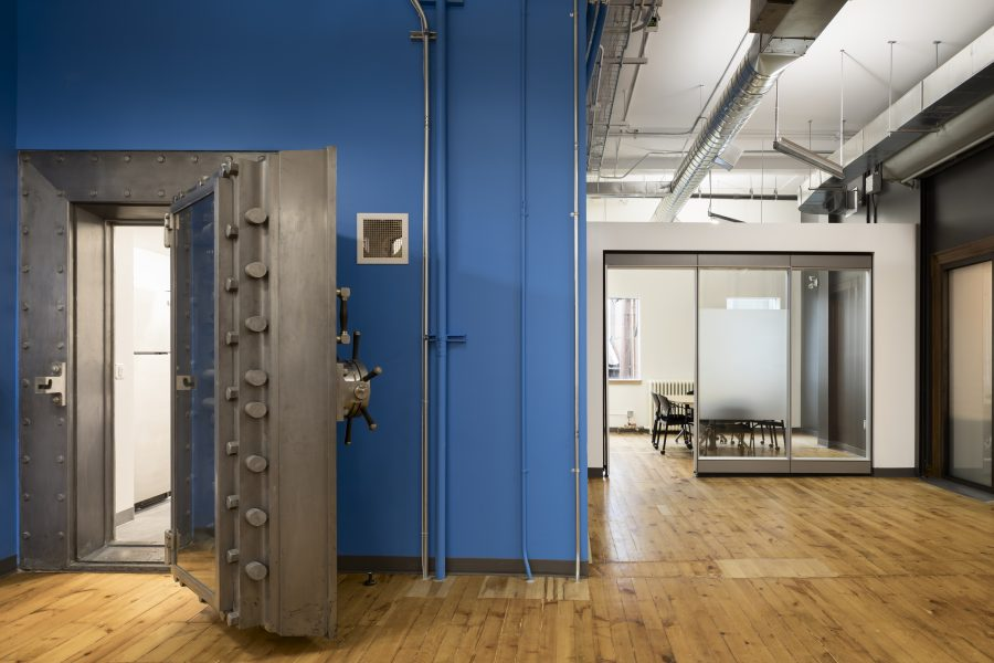 14 Erb St. West is a flexible work and meeting space with multipurpose collaborative furniture. A reclaimed bank vault door provides access the work spaces. Meeting rooms are located around the perimeter of the building with glazing to allow natural light deep into the building's core.