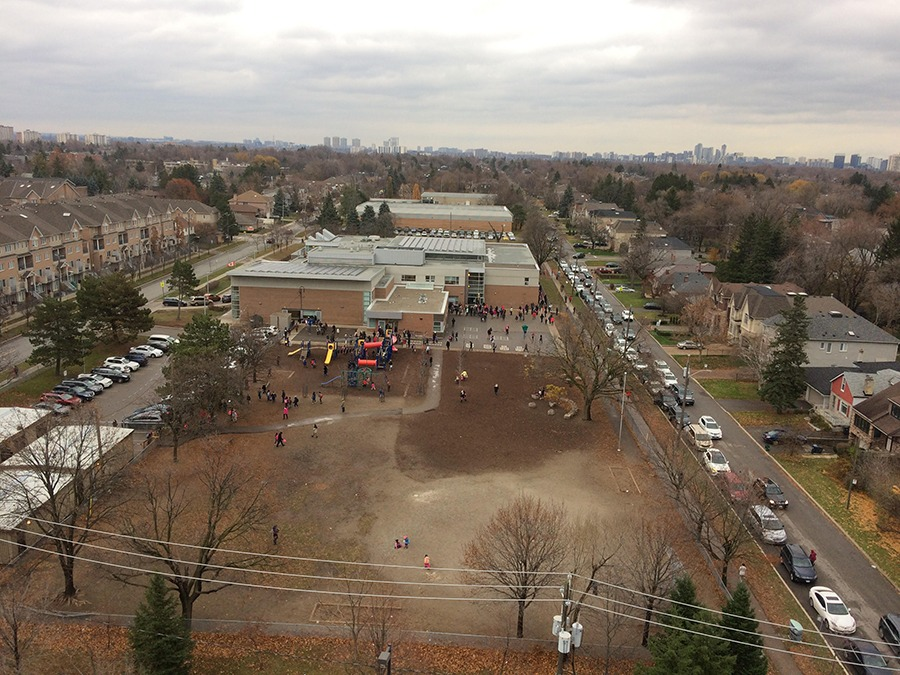 McKee Public School, along with the resulting heavy morning congestion, can be seen from Marc Bhalla's North York condo, located across the street. Even in such close proximity, zoning laws dictate the condo kids must be bussed elsewhere. (Photo by Marc Bhalla)
