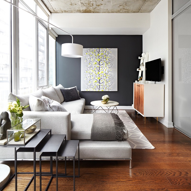 An art piece to give the black wall a bit of pop, some couch accessorizing, and a sleek side table with some greenery add a pop of colour to the neutral paint tone. (Photo by Lisa Petrole)