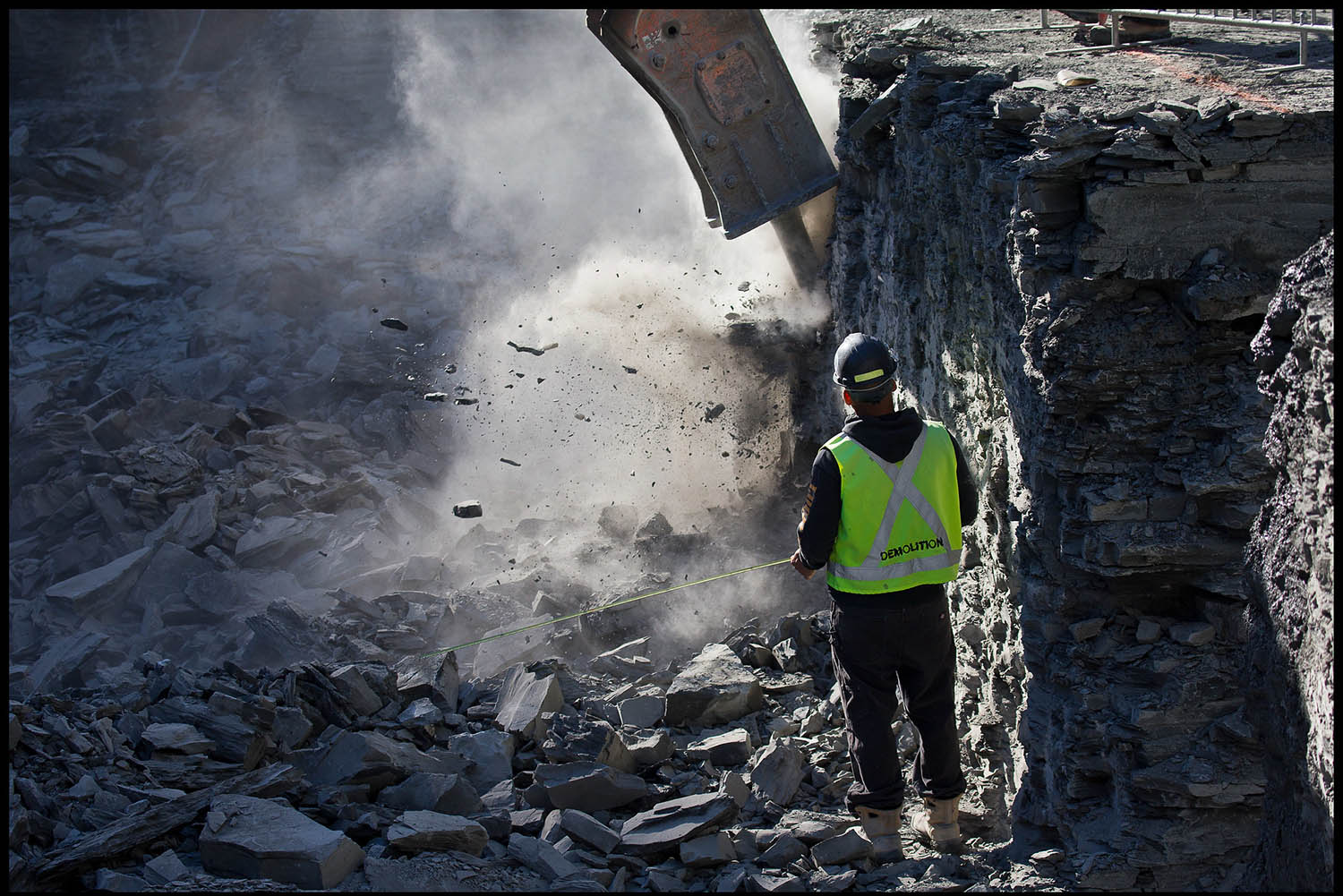 The excavator chisels its way through the shale bedrock of Toronto's South Core, an area of the city south of King Street down to the lake, where the shale bedrock is close to the surface at the lakefront about 10 metres down. Chiseling out the ancient sedimentary rock is the only practical way to excavate the site when deep enough to reach the shale.