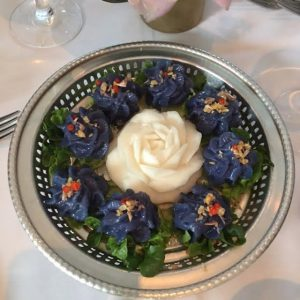 Chor ladda, a flower-shaped dumpling made from butterfly pea-dyed jasmine rice and topped with crispy Thai garlic